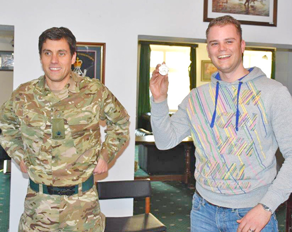 Martin Pankoke is awarded the Commanding Officer's coin for exceptional marksmanship by Maj Ben Casson, OC B Coy 5 RIFLES