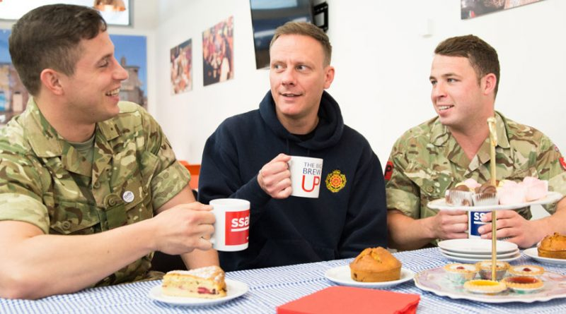 SSAFA Ambassador, Coronation Street actor Anthony Cotton, centre, enjoying a brew with soldiers during one of the Big Brew Up events