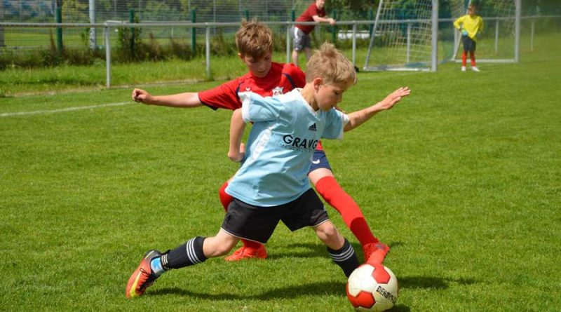 Paderborn United player Jake looks to tackle his opponent